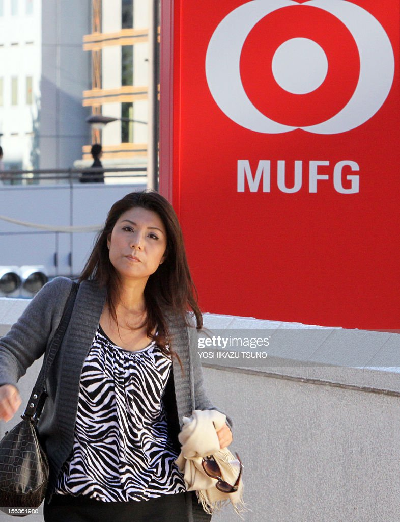A pedestrian passes before a branch of Mitsubishi UFJ bank in Tokyo on November 14, 2012. Japanese mega bank Mitsubishi UFJ Financial Group (MUFG) reported double-digit tumbles in their first-half net profit, owing partly to declines in their stock holdings. MUFG saw its profit in the six months to September dive 58 percent to 90.48 billion yen (3.6 billion USD) in its fiscal first half to September, well down from 696.09 billion in the same period last year. AFP PHOTO / Yoshikazu TSUNO