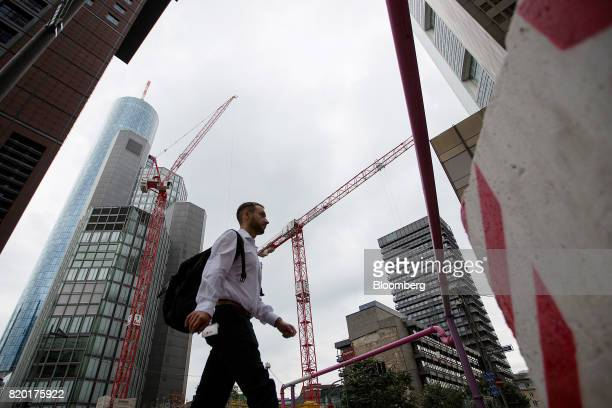 A pedestrian passes by skyscrapers and construction cranes in Frankfurt Germany on Thursday July 20 2017 Frankfurt has emerged as a winner of the...
