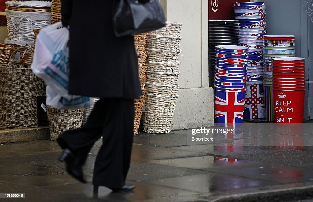 A pedestrian passes dustbins decorated with the British Union Jack flag outside a store in Guildford, U.K., on Friday, Dec. 14, 2012. Standard & Poor's lowered its outlook on Britain's top credit rating to negative, citing weak economic growth and a worsening debt profile. Photographer: Simon Dawson/Bloomberg via Getty Images