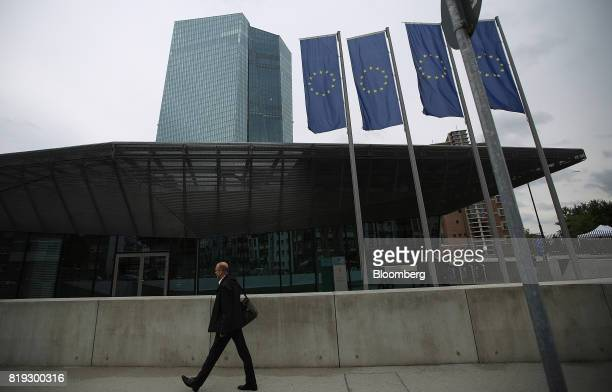 A pedestrian passes European Union banners flying outside the European Central Bank headquarters in Frankfurt Germany on Thursday July 20 2017 When...