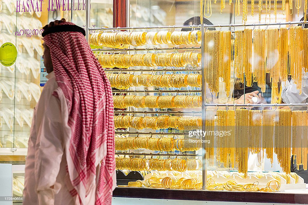 A pedestrian passes gold jewelry on display in the windows of a gold store in the Dubai Gold Souk in the Deira district of Dubai, United Arab Emirates, on Tuesday, July 2, 2013. Gold swung between gains and losses in London as investors weighed prospects for increased physical demand against a slowing stimulus in the U.S. Photographer: Duncan Chard/Bloomberg via Getty Images