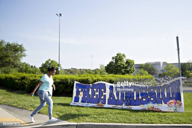 A pedestrian passes in front of a 'Free Admission' sign during the Dreamland Amusements carnival at the Marley Station Mall in Glen Burnie Maryland...