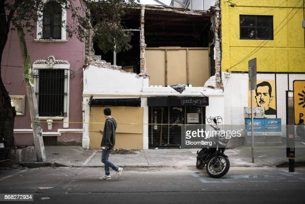 A pedestrian passes in front of a hair salon damaged from the earthquake in the Roma neighborhood of Mexico City Mexico on Friday Oct 27 2017 The...