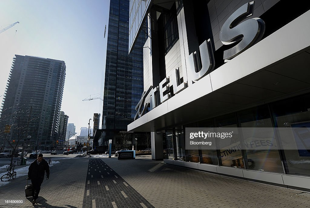 A pedestrian passes in front of the Telus Corp. building in Toronto, Ontario, Canada, on Wednesday, Feb. 13, 2013. Telus Corp. is scheduled to release earnings data on Feb. 15. Photographer: Aaron Harris/Bloomberg via Getty Images