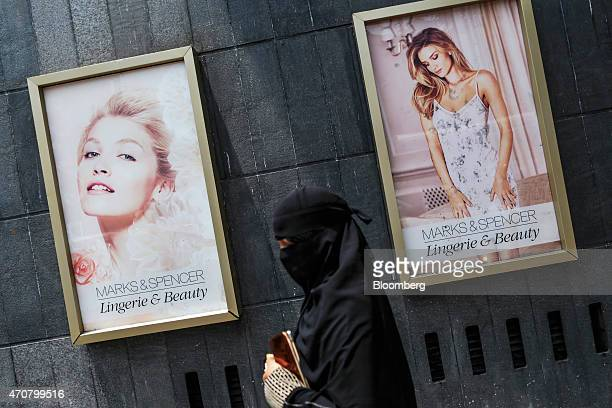 A pedestrian passes 'Lingerie Beauty' advertisements outside a Marks Spencer Reliance India Pvt store in the Bandra area of Mumbai India on Wednesday...