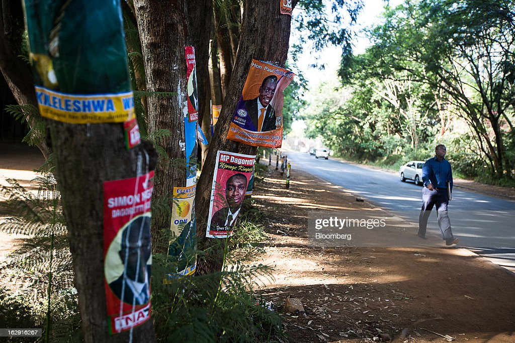 A pedestrian passes political election posters hanging from trees on a roadside ahead of the presidential election in Nairobi, Kenya, on Friday, March 1, 2013. Next week's presidential vote will be the first since disputed elections in 2007 triggered ethnic fighting in which more than 1,100 people died and another 350,000 fled their homes. Photographer: Trevor Snapp/Bloomberg via Getty Images