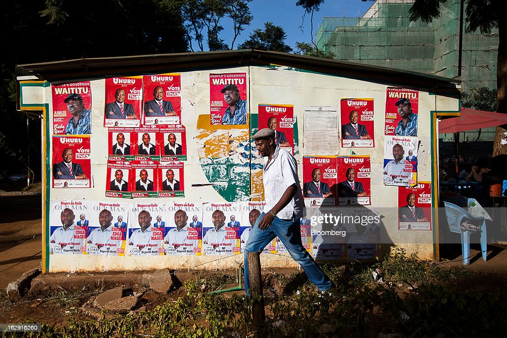 A pedestrian passes political election posters pasted to a building ahead of the presidential election in Nairobi, Kenya, on Friday, March 1, 2013. Next week's presidential vote will be the first since disputed elections in 2007 triggered ethnic fighting in which more than 1,100 people died and another 350,000 fled their homes. Photographer: Trevor Snapp/Bloomberg via Getty Images