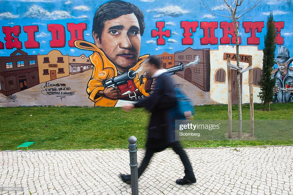 A pedestrian passes political graffiti depicting Portugal's Prime Minister Pedro Passos Coelho as a cowboy in the Wild West on a wall in Lisbon, Portugal, on Saturday, March 2, 2013. Prime Minister Pedro Passos Coelho is battling rising joblessness and lower demand from European trading partners as he raises taxes to meet the terms of a 78 billion-euro ($104 billion) aid plan from the European Union and the International Monetary Fund. Photographer: Mario Proenca/Bloomberg via Getty Images