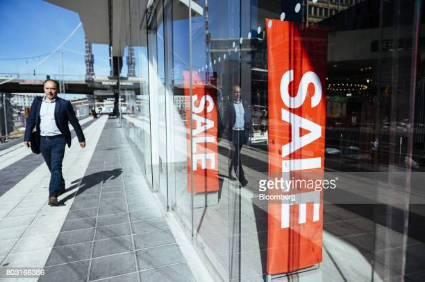A pedestrian passes sales signs in the window of a Hennes Mauritz AB fashion store in Stockholm Sweden on Wednesday June 28 2017 Costcontrol is the...