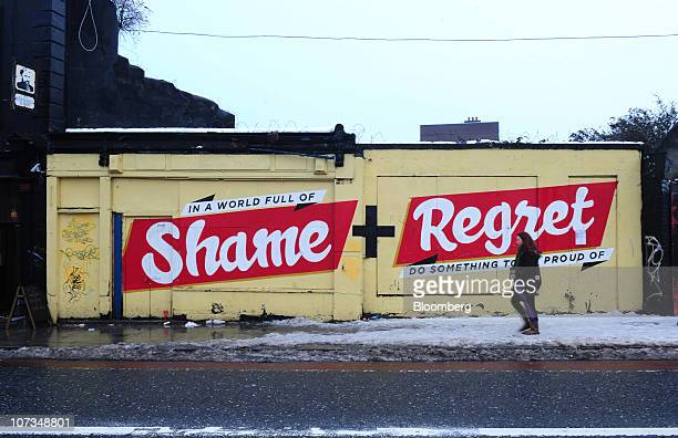 A pedestrian passes street art displayed on a building in Dublin Ireland on Saturday Dec 4 2010 Irish Prime Minister Brian Cowen's government will...