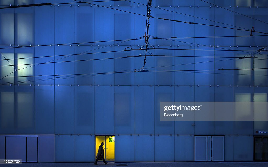 'BEST PHOTOS OF 2012' (): A pedestrian passes the BNP Paribas SA office in Geneva, Switzerland, on Monday, Oct. 29, 2012. Geneva's banks employed 502 fewer people at the end of June compared with a year earlier as foreign wealth managers cut jobs and shifted employees to other locations, a survey by the city's financial lobby group shows. Photographer: Valentin Flauraud/Bloomberg via Getty Images