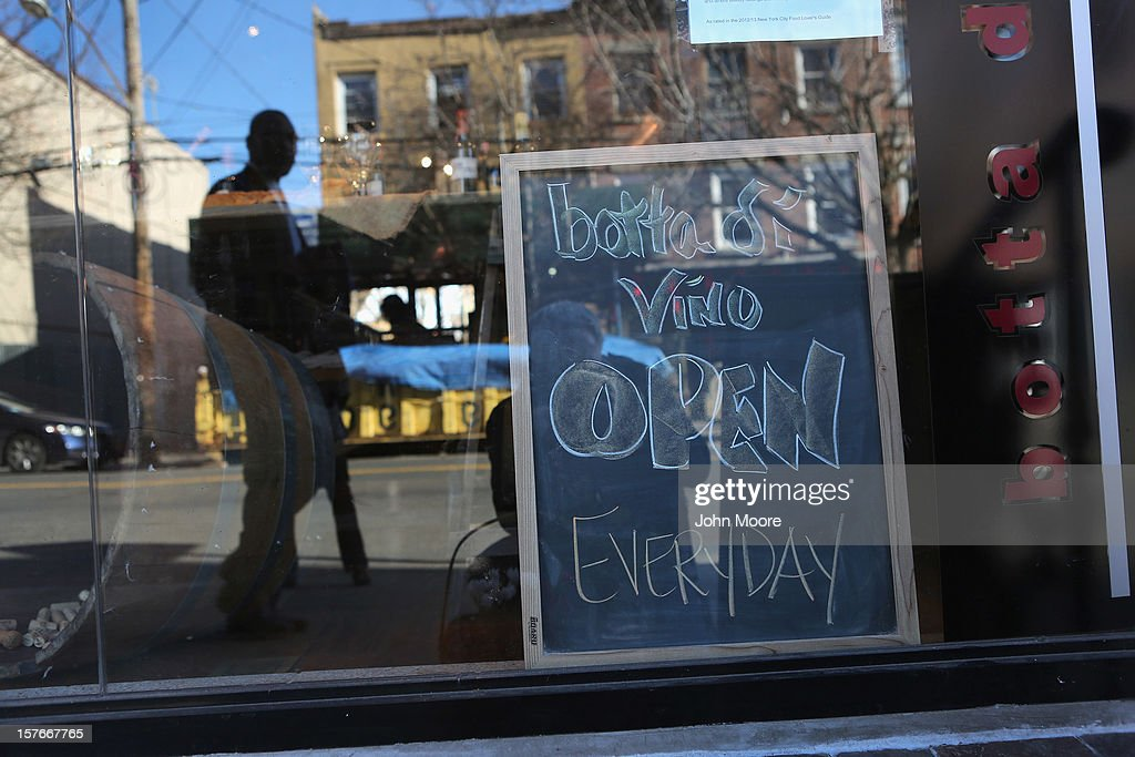 A pedestrian passes the Botta di Vino wine store in the Red Hook neighborhood of Brooklyn on December 5, 2012 in New York City. The owner Triciann Botta said that she reopened her shop soon after the storm, but more than a month after superstorm Sandy flooded the area, many others remain closed, pending repairs.
