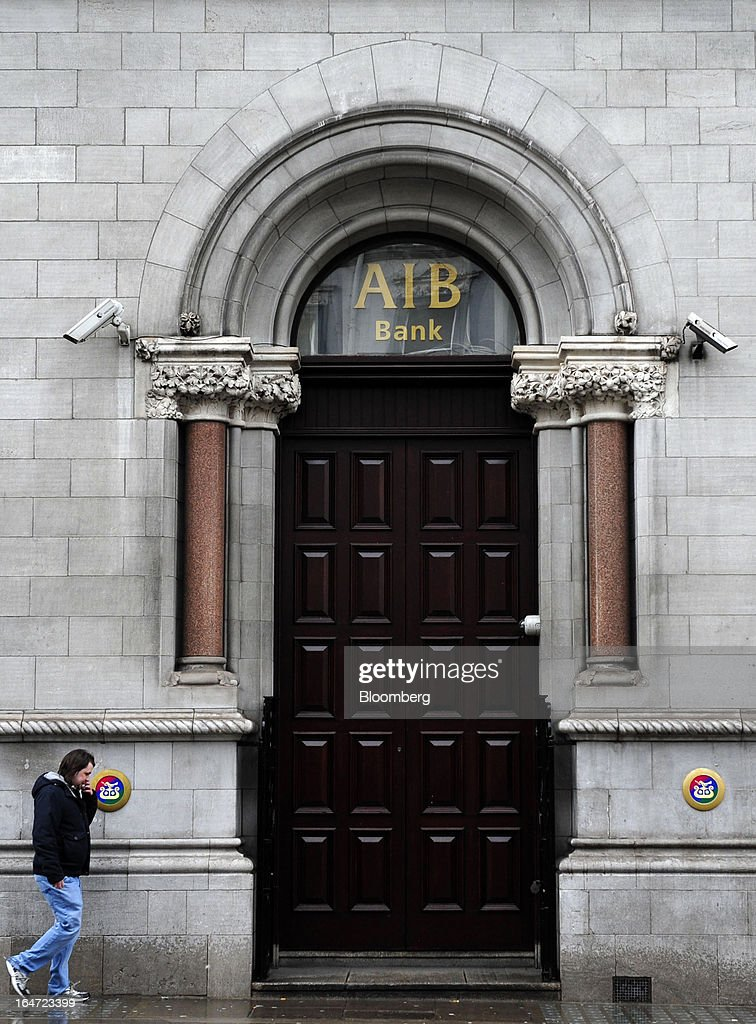 A pedestrian passes the closed doors of an Allied Irish Banks Plc (AIB) branch in Dublin, Ireland, on Wednesday, March 27, 2013. Allied Irish Banks Plc, which cost taxpayers about 21 billion euros ($27 billion) to rescue, said its annual loss widened as a decline in bad loan losses failed to offset dwindling gains from buying back its own debt. Photographer: Aidan Crawley/Bloomberg via Getty Images
