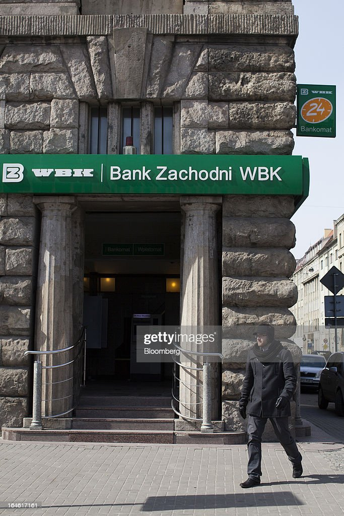 A pedestrian passes the entrance to a Bank Zachodni WBK SA branch in Wroclaw, Poland, on Monday, March 25, 2013. KBC Groep NV of Belgium and Banco Santander SA of Spain raised 4.89 billion zloty ($1.51 billion) from the sale of a stake in Bank Zachodni WBK SA, Poland's third-largest lender. Photographer: Bartek Sadowski/Bloomberg via Getty Images