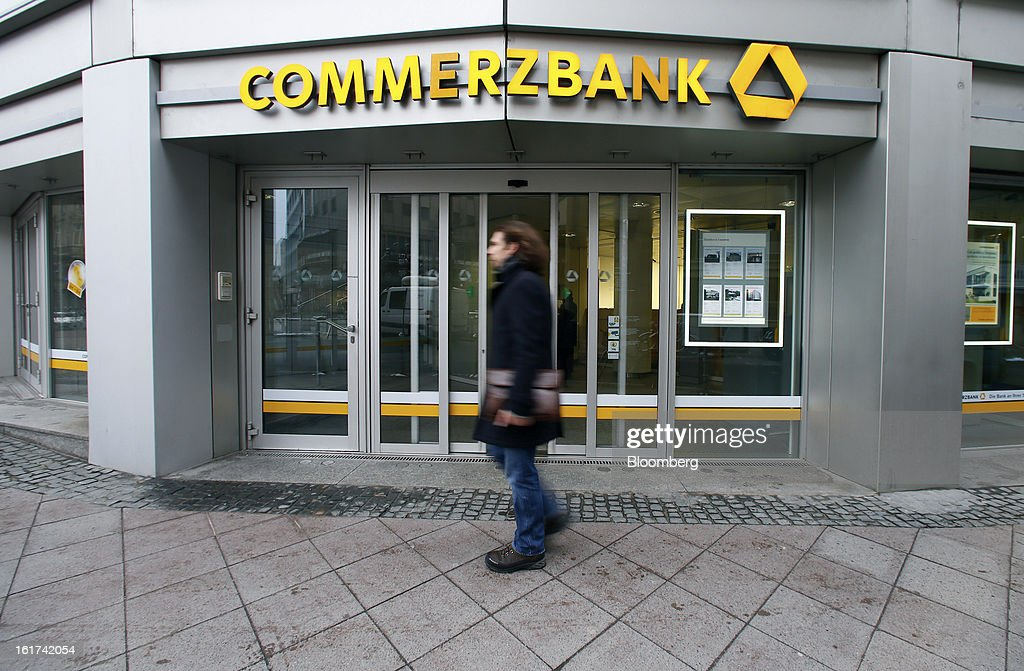 A pedestrian passes the entrance to a Commerzbank AG bank branch in Frankfurt, Germany, on Friday, Feb. 15, 2013. Commerzbank AG Chief Executive Officer Martin Blessing gave up his bonus for last year and cut the payouts by an average 17 percent across the firm, warning of higher costs and more pressure on revenue. Photographer: Ralph Orlowski/Bloomberg via Getty Images