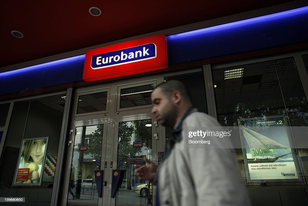 A pedestrian passes the entrance to a Eurobank Ergasias SA branch in Athens, Greece, on Tuesday, Jan. 22, 2013. Euro-area finance ministers blessed the next disbursement of emergency aid for Greece, highlighting the goodwill that led to the unblocking of loans last month for Prime Minister Antonis Samaras's government. Photographer: Kostas Tsironis/Bloomberg via Getty Images