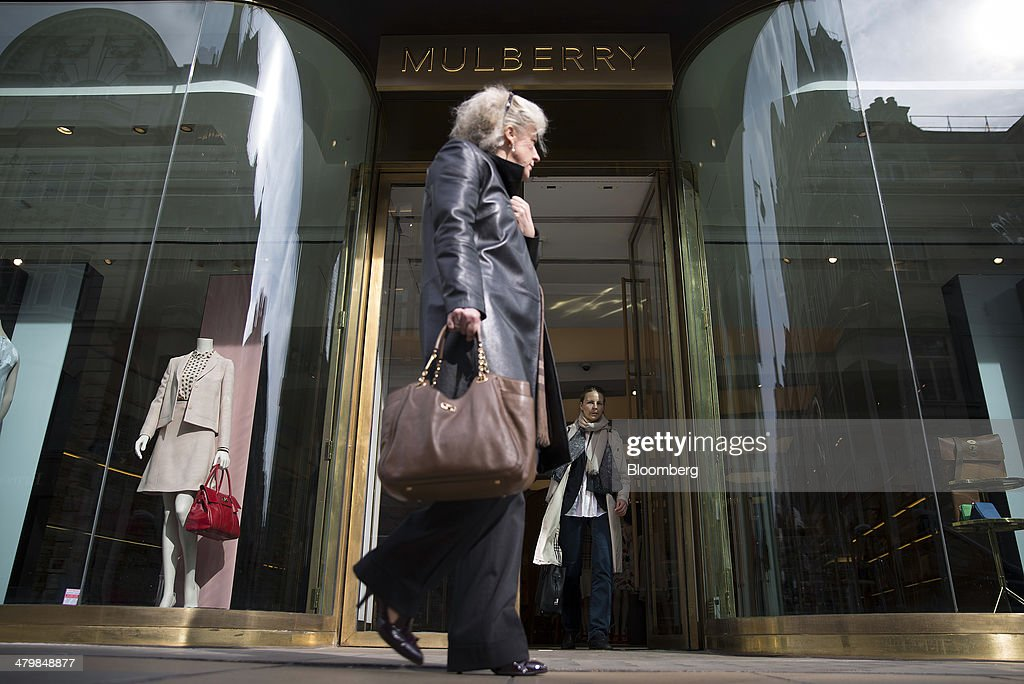 A pedestrian passes the entrance to a Mulberry Group Plc luxury store on New Bond Street in London, U.K., on Thursday, March 20, 2014. Mulberry Group said Bruno Guillon will step down as chief executive officer after two years during which the British luxury handbag maker lost two-thirds of its market value. Photographer: Simon Dawson/Bloomberg via Getty Images