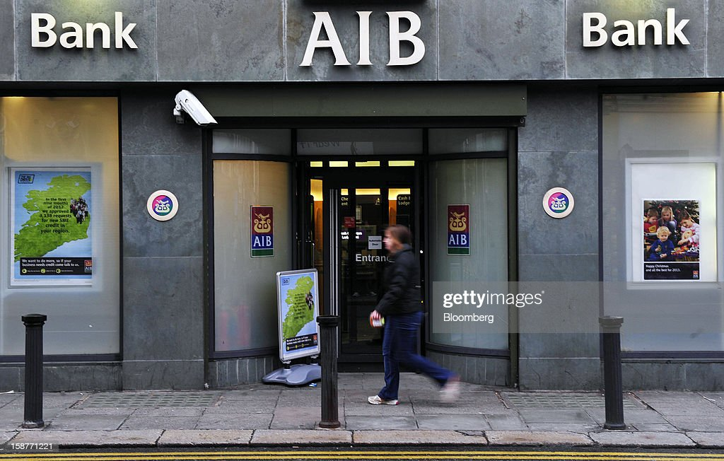 A pedestrian passes the entrance to an Allied Irish Bank (AIB) branch in Dublin, Ireland, on Friday, Dec. 28, 2012. Ireland will take over the EU presidency in January as the euro-area wrestles with putting the European Central Bank in charge of lenders within the currency union and other participating nations. Photographer: Aidan Crawley/Bloomberg via Getty Images