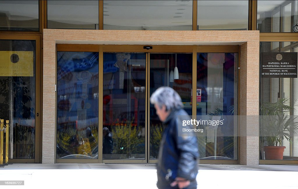 A pedestrian passes the entrance to the headquarters of Macedonia's central bank in Skopje, Macedonia, on Sunday, March 17, 2013. Macedonia's economy contracted by a real 0.3% on the year in 2012, compared to a growth of 2.8% a year earlier, an estimate released by the country's statistics office showed. Photographer: Oliver Bunic/Bloomberg via Getty Images