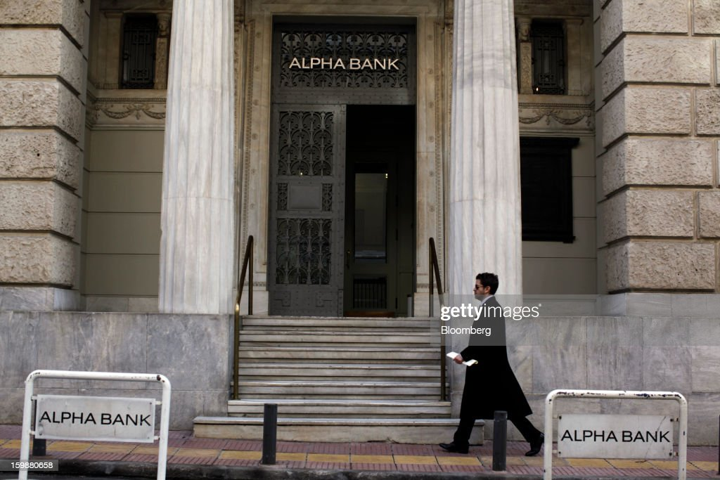 A pedestrian passes the entrance to the offices of Alpha Bank AE in Athens, Greece, on Tuesday, Jan. 22, 2013. Euro-area finance ministers blessed the next disbursement of emergency aid for Greece, highlighting the goodwill that led to the unblocking of loans last month for Prime Minister Antonis Samaras's government. Photographer: Kostas Tsironis/Bloomberg via Getty Images