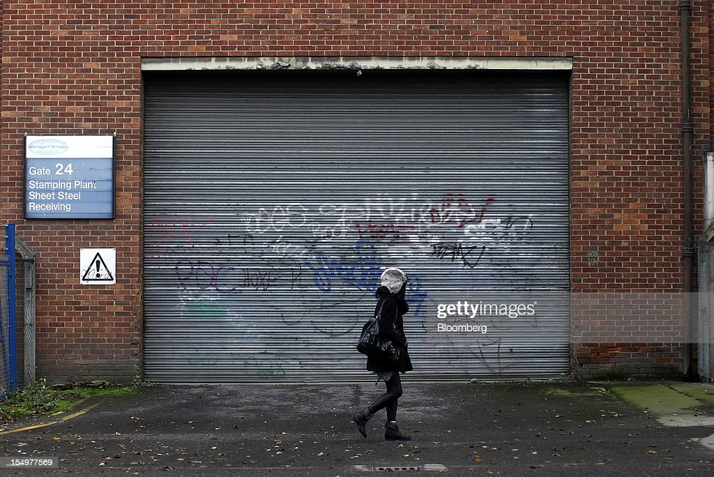 A pedestrian passes the graffiti-damaged doorway to a delivery entrance at the stamping operations plant in the Ford Motor Co. automobile factory in Dagenham, U.K., on Monday, Oct. 29, 2012. Ford Motor Co. will shut three European plants, its first factory closings in the region in a decade, and cut 5,700 jobs to stem losses that the carmaker predicts will total more than $3 billion over two years. Photographer: Simon Dawson/Bloomberg via Getty Images