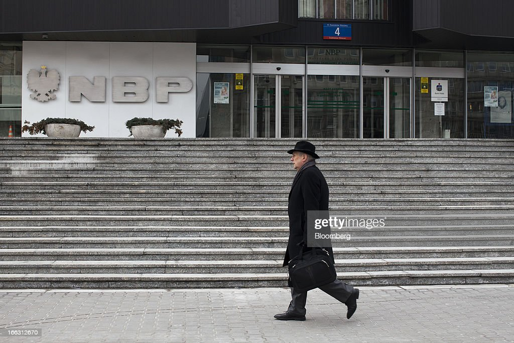 A pedestrian passes the headquarters of the National Bank of Poland (NBP) in Warsaw, Poland, on Wednesday, April 10, 2013. Poland's central bank kept interest rates unchanged at a record-low 3.25 percent yesterday. Photographer: Bartek Sadowski/Bloomerg