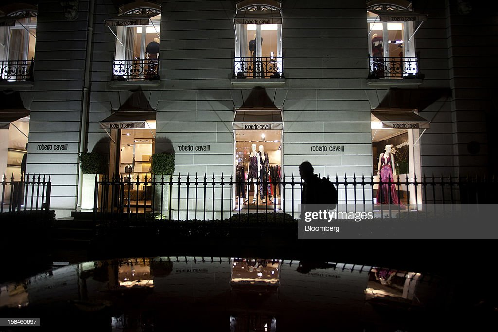A pedestrian passes the illuminated Roberto Cavalli SpA store on Avenue Montaigne in Paris, France, on Saturday, Dec. 15, 2012. The French minister for energy and environment unveiled a proposal for lights in and outside shops, offices, and public buildings -- including the flagship Louis Vuitton store and the Lido cabaret house on Paris's Avenue des Champs Elysees -- to be turned off between 1 a.m. and 7 a.m. starting in July. Photographer: Balint Porneczi/Bloomberg via Getty Images