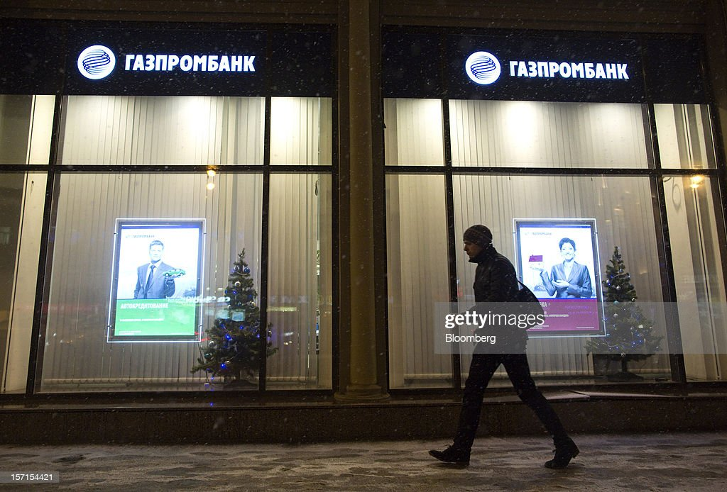 A pedestrian passes the illuminated window of an OAO Gazprombank in Moscow, Russia, on Wednesday, Nov. 28, 2012. Bank Rossii proposes government create rule limiting increases of budget funds held at central bank, RIA Novosti reports, citing First Deputy Chairman Alexey Ulyukayev. Photographer: Andrey Rudakov/Bloomberg via Getty Images