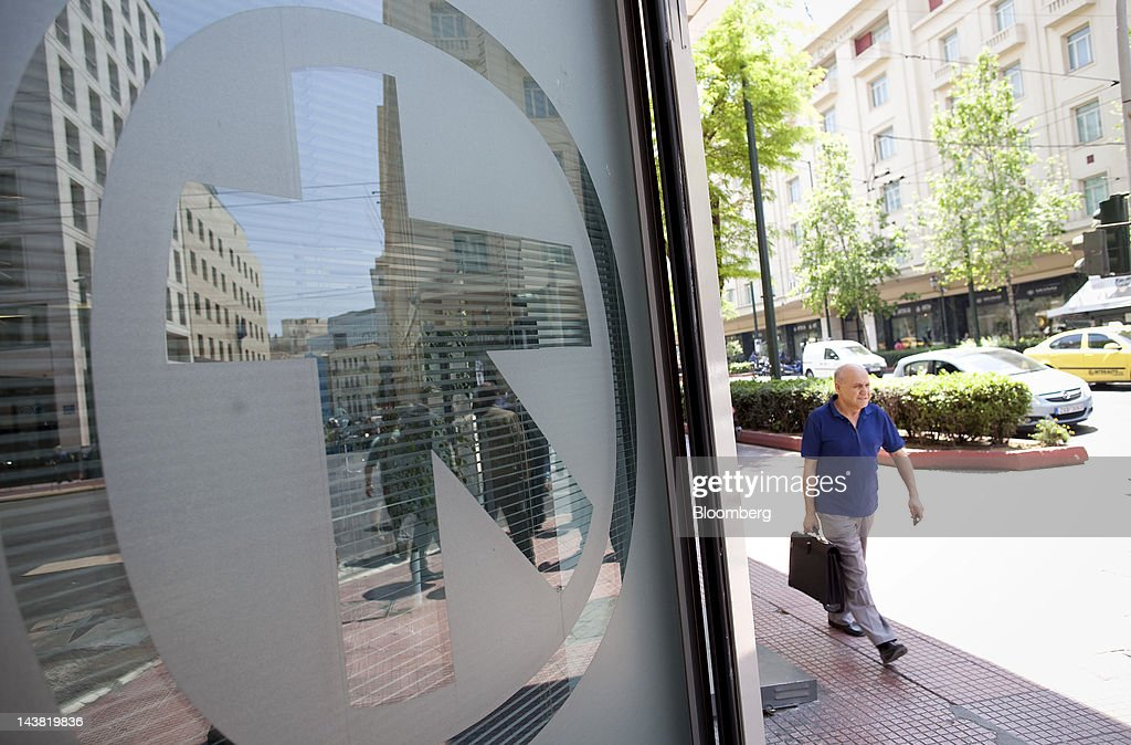 A pedestrian passes the logo of Alpha Bank AE on the window of a branch in Athens, Greece, on Friday, May 4, 2012. European stocks dropped as investors awaited today's American payrolls report and elections in France, Greece, Italy and Germany this weekend. Photographer: Simon Dawson/Bloomberg via Getty Images