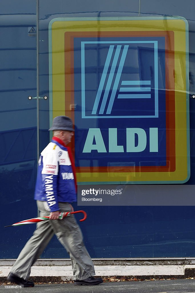 A pedestrian passes the window of a supermarket operated by Aldi Group, Germany's biggest discount-food retailer, in this arranged photograph in Manchester, U.K., on Thursday, Oct. 4, 2012. U.K. shop-price inflation slowed in September as retailers offered discounts to attract cash-strapped consumers, the British Retail Consortium said. Photographer: Paul Thomas/Bloomberg via Getty Images