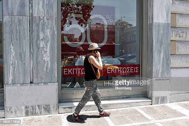 A pedestrian passes the window of a Zara Home store operated by Inditex SA advertising 50% discounts during the summer sales in Athens Greece on...