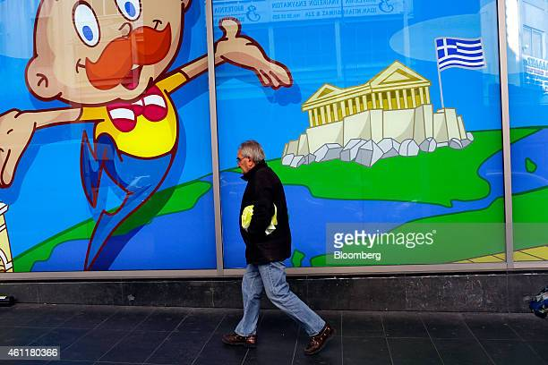 A pedestrian passes the window panel of a toy store decorated with a cartoon character beside the Greek flag on Acropolis Hill in Athens Greece on...