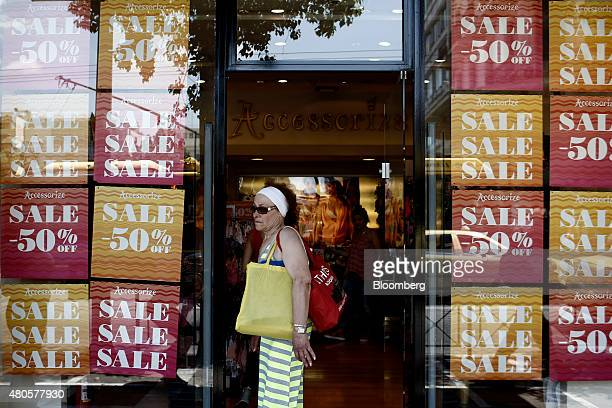 A pedestrian passes the windows of an Accessorize accessories store covered with advertisements for 50% discounts during the summer sales in Athens...