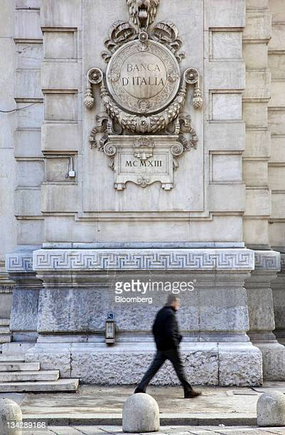 A pedestrian passes under a logo on the wall of the Banca d'Italia Italy's central bank in Milan Italy on Tuesday Nov 29 2011 Italian Prime Minister...