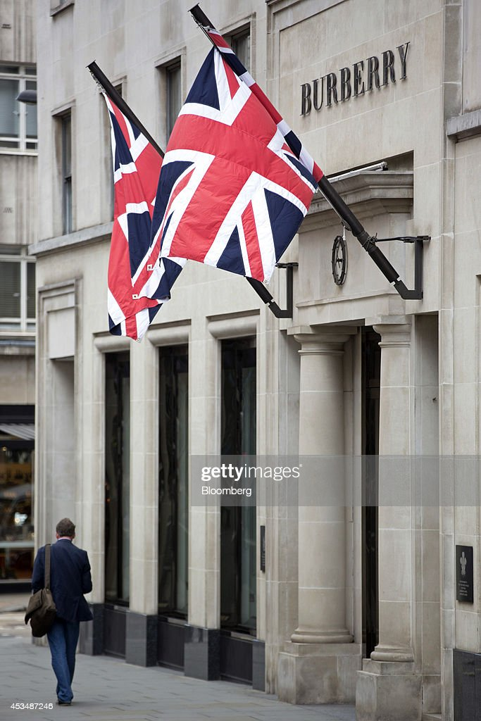 A pedestrian passes Union flags as they fly above the entrance to a Burberry Group Plc store, locted inside a commercial real estate building that forms part of the Pollen Estate, on New Bond Street in London, U.K., on Monday, Aug. 11, 2014. Norway's sovereign wealth fund, Norges Bank Investment Management, the world's largest, bought a stake in the Pollen Estate in London's Mayfair district for 343 million pounds ($576 million), expanding its property holdings in the U.K. capital. Photographer: Jason Alden/Bloomberg via Getty Images
