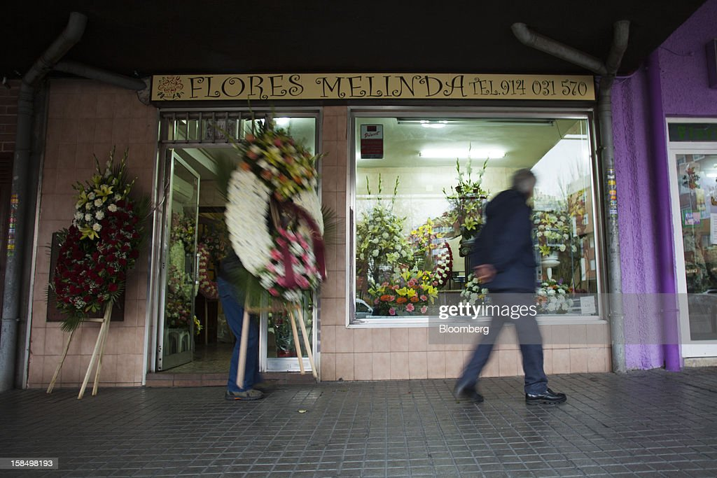 A pedestrian passes wreaths on display in the window of a funeral flower store in Madrid, Spain, on Monday, Dec. 17, 2012. Spain, responding to street protests and reports of suicides linked to foreclosures, introduced rules to help protect families from eviction, increasing the risk of creditor losses and weakening an already fragile banking system. Photographer: Angel Navarrete/Bloomberg via Getty Images