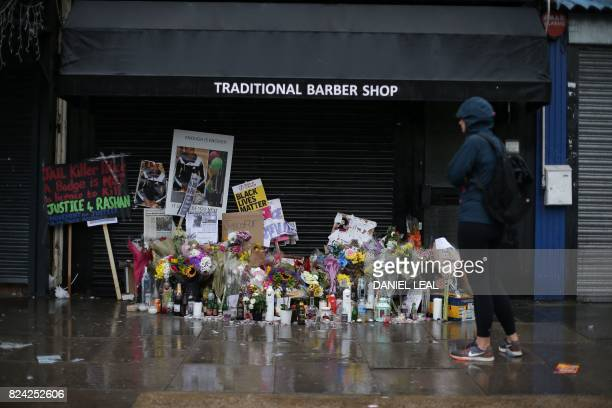 A pedestrian pauses in front of a pile of floral tributes and candles for Rashan Charles whose death after being followed by police into a...