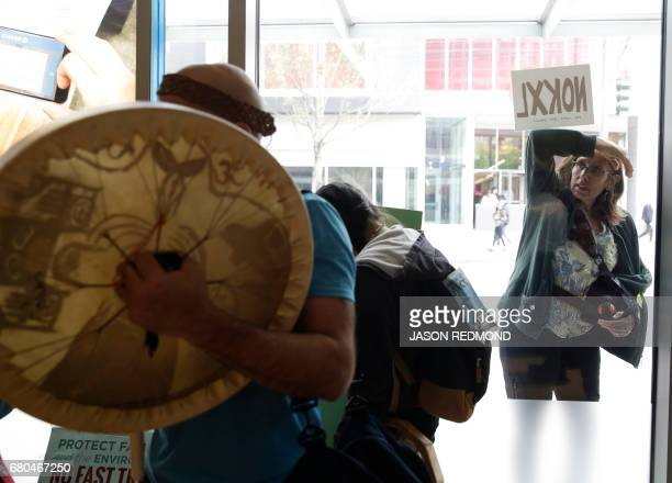 A pedestrian peers through a window as indigenous leaders and climate activists disrupt business at a Chase Bank branch in Seattle on May 8 2017...