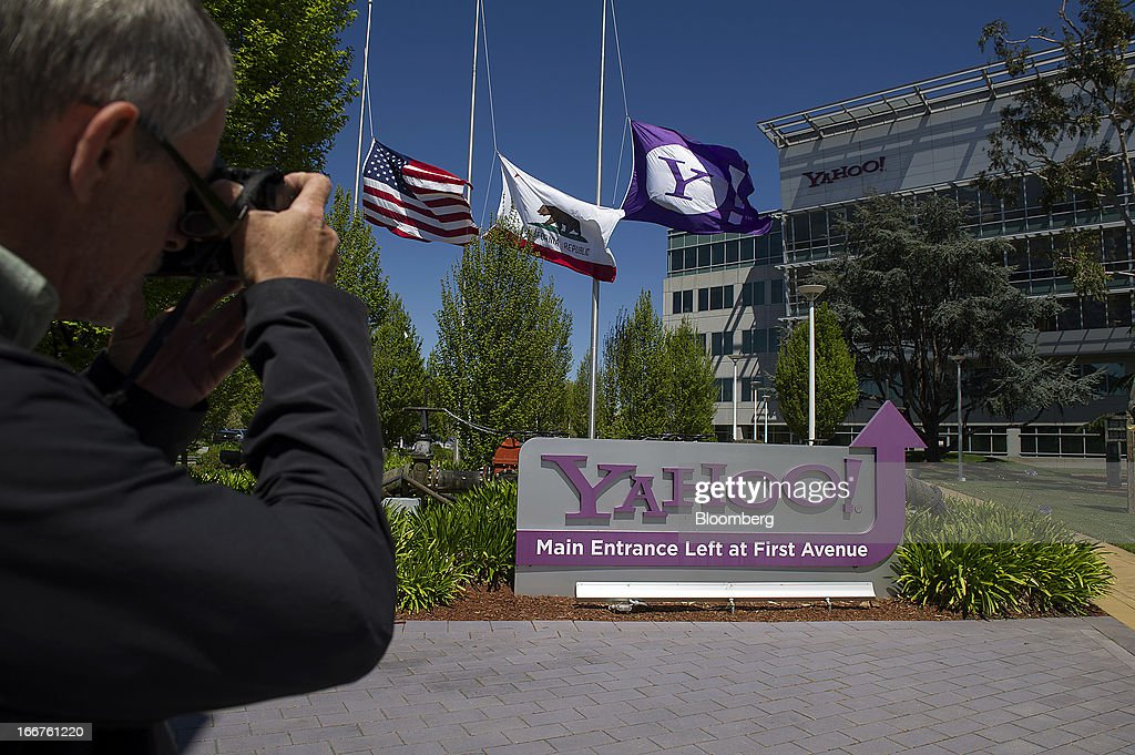 A pedestrian photographs Yahoo! Inc. signage displayed at the company's headquarters in Sunnyvale, California, U.S., on Tuesday, April 16, 2013. Yahoo! Inc., the biggest U.S. Web portal, forecast sales that fell short of analysts' estimates as it continued to lose advertisers to Google Inc. and Facebook Inc. Photographer: David Paul Morris/Bloomberg via Getty Images