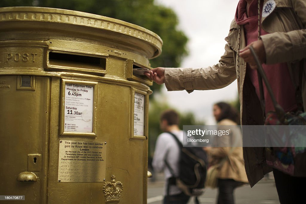 A pedestrian posts a letter into a Royal Mail Group Ltd. double aperture pillar box, painted gold to celebrate the London 2012 Olympic and Paralympic Games, in London, U.K., on Thursday, Sept. 12, 2013. Royal Mail Group Ltd., the U.K.'s 360-year-old postal service, intends to hold an initial public offering of a majority stake 'in the coming weeks' to help the company gain a competitive edge against European rivals. Photographer: Matthew Lloyd/Bloomberg via Getty Images