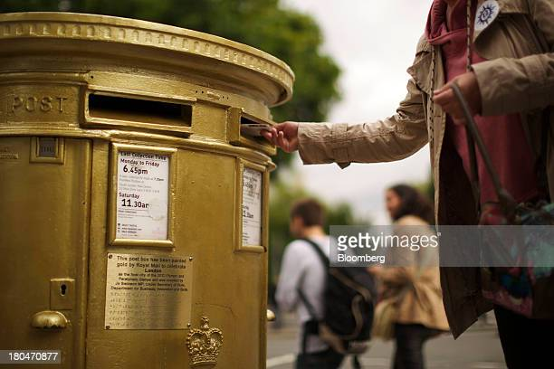 A pedestrian posts a letter into a Royal Mail Group Ltd double aperture pillar box painted gold to celebrate the London 2012 Olympic and Paralympic...
