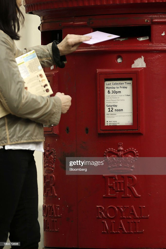 A pedestrian posts a letter into a Royal Mail Group Ltd. double aperture pillar box in London, U.K., on Thursday, Sept. 12, 2013. Royal Mail Group Ltd., the U.K.'s 360-year-old postal service, intends to hold an initial public offering of a majority stake 'in the coming weeks' to help the company gain a competitive edge against European rivals. Photographer: Matthew Lloyd/Bloomberg via Getty Images