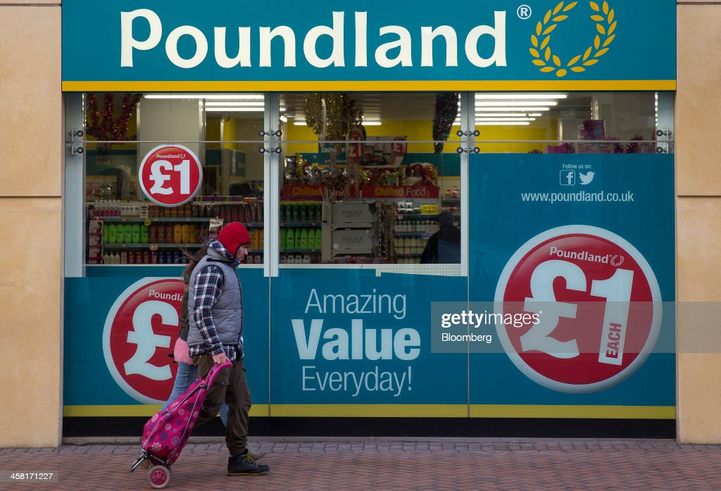 A pedestrian pulls a shopping cart as he passes a Poundland discount store, operated by Poundland Holdings Ltd., in Birmingham, U.K., on Friday, Dec. 20, 2013. U.K. discount retailer Poundland has hired Rothschild to manage its IPO, according to the Sunday Times newspaper. Photographer: Simon Dawson/Bloomberg via Getty Images