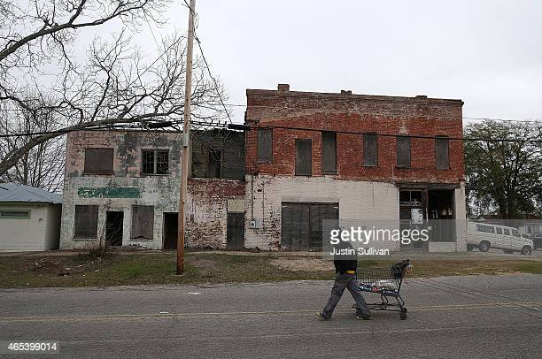 A pedestrian pulls a shopping cart by vacant buildings on March 6 2015 in Selma Alabama 50 years after the historic civil rights march from Selma to...