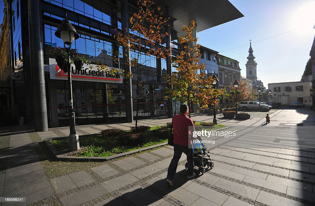 A pedestrian pushes a baby stroller passed a UniCredit SpA office in Belgrade, Serbia, on Sunday, Oct. 20, 2013. Serbia's government revealed a salvo of measures to bring the public finance deficit and debt back under control by 2017 after the head of the largest coalition party warned the country was on the brink of insolvency. Photographer: Oliver Bunic/Bloomberg via Getty Images
