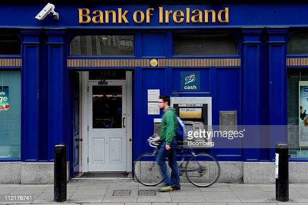 A pedestrian pushes a bicycle past a Bank of Ireland automated teller machine outside a company branch in Dublin Ireland on Thursday April 14 2011...