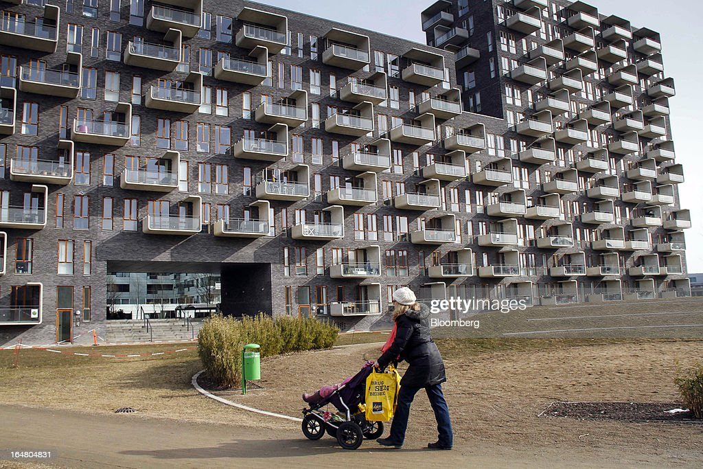 A pedestrian pushes a child in a stroller near a newly-constructed residential apartment block in Orestad on the outskirts of Copenhagen, Denmark, on Thursday, March 28, 2013. Denmark's government rejected a plan by mortgage banks last week to split troubled loans and extend interest-only terms for amounts below an 80 percent loan-to-value limit. Photographer: Freya Ingrid Morales/Bloomberg via Getty Images