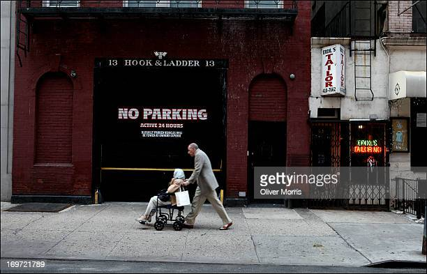 A pedestrian pushes a woman in a wheelchair past the 'No Parking' sign on the Hook and Ladder Company No 13 door Manhattan's Upper East Side...