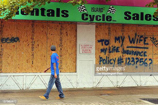 A pedestrian reads a sign on a boardedup shop as he walks by Friday in Ocean City Md