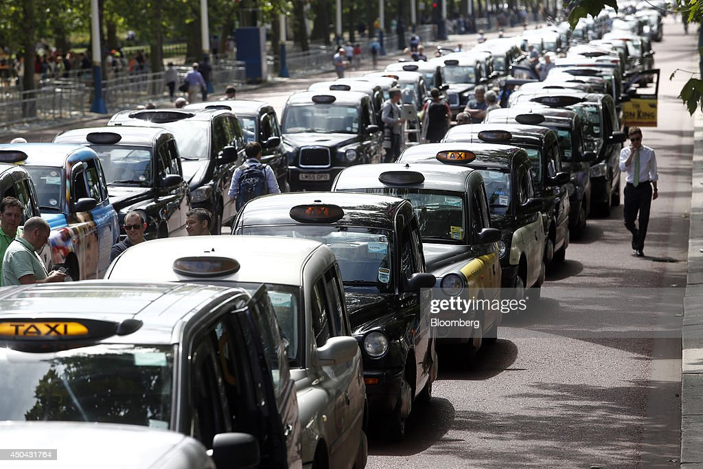A pedestrian, right, walks past a line of London taxi cabs parked along The Mall, leading away from Buckingham Palace, during a protest against Uber Technologies Inc.'s car sharing service in London, U.K., on Wednesday, June 11, 2014. Traffic snarled in parts of Madrid and Paris today, with a total of more than 30,000 taxi and limo drivers from London to Berlin blocking tourist centers and shopping districts. Photographer: Simon Dawson/Bloomberg via Getty Images